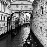 In 2019, I was in Venice (Italy) traveling with my parents and a group of friends. We were walking around the city and I saw the beauty of the place. The image shows two gondolas with couples strolling through the city and passing under the famous Bridge of Sighs, which connected a prison with the Palazzo Ducale. The bridge's name is based on a legend that the prisoners crossed the bridge, taking their last breath, as it would be the last time they would see the outside world.